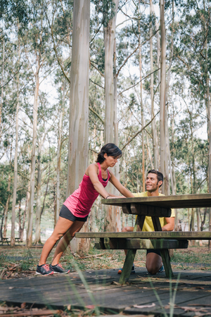 Sporty woman exercising with fitness trainer outdoor in forest. Sport runner female doing push ups exercise with her coach outside during workout strenght routine.
