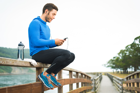 Outdoor runner man sitting on wooden walkway listening looking and touching his phone with water bottle and white towel. Fitness fit male motivated for outside workout exercises.