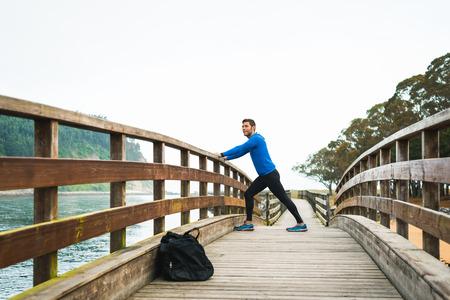 elasticidad: deportes Fit hombre estirando las piernas antes de un entrenamiento de correr al aire libre en un día nublado de otoño con una bolsa de deporte en una pasarela de madera. Hombre deportivo Fitness en Rodiles, Asturias.