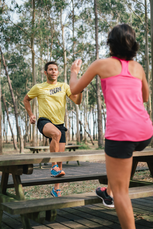 Runner couple doing toe taps hiit exercise for warming up before running.  Trainer showing fitness workout at the same time. Banco de Imagens