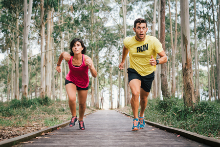 Fitness couple starting running race on wooden walkway on an outdoor park challenging in powerful confident sprint  during training workout in Rodiles, Asturias. Banco de Imagens