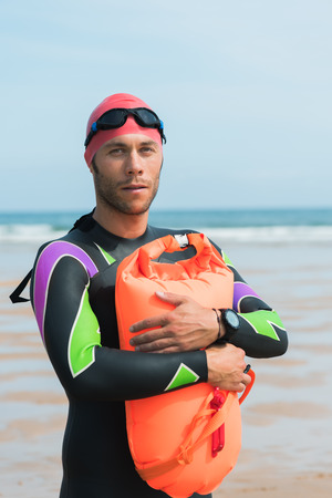 Portrait of a strong swimmer embracing swimming safety buoy motivated for his open water workout routine with goggles, cap and wet suit on a beach.