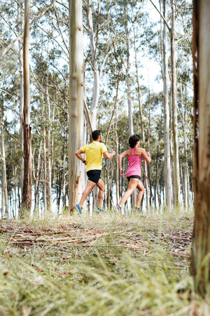 Couple doing running exercises workout training outdoor on forest. Young caucasian runner couple  jogging outside on beautiful nature scene. Fitness healthy lifestyle.