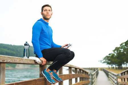 Outdoor runner man sitting on wooden walkway listening music on phone with water bottle and white towel. Fitness fit male motivated for outside workout exercises.