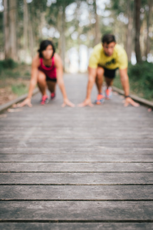 Defocused Fitness couple ready for running race on wooden walkway on an outdoor park looking each other challenging in powerful confident starting line pose in Rodiles, Asturias.