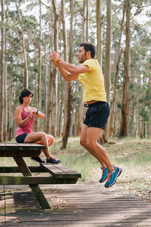 simultaneously: Sports coach woman trainer checking watch counter while her disciple is jumping on a wooden bench outdoor on a forest. Sporty couple exercising runner strength workout. Stock Photo