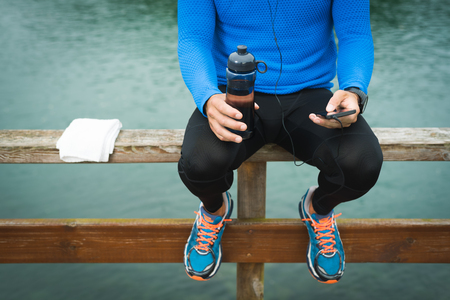Fitness man looking to the phone for motivation before outdoor workout. Sporty male athlete looking his smartphone with earphones holding water bottle.