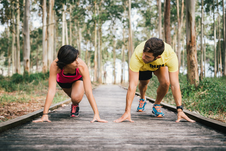 Fitness couple ready for running race on wooden walkway on an outdoor park looking each other challenging in powerful confident starting line pose in Rodiles, Asturias.