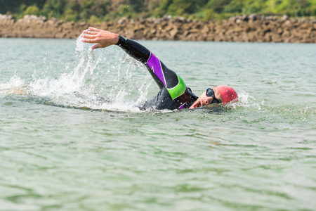 Swimmer. Man swimming Freestyle strokes in open water outdoor competition. Competitive triathlete male sport swimmer wearing swimming goggles, cap and wet suit taking air. Banco de Imagens