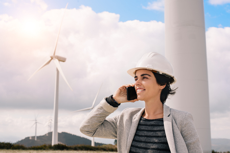 Smiling engineer woman talking on phone with safety helmet at wind turbine farm in eolic park generating energy with air flow with spinning blades. Clean renewable green wind power concept.