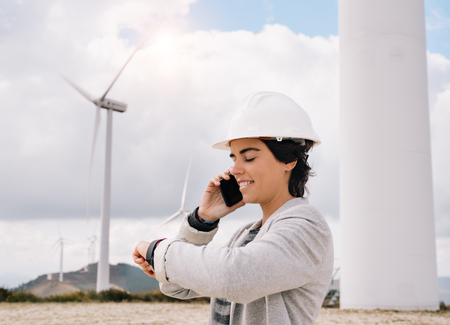 Smiling engineer woman talking on phone with safety helmet looking to her watch at wind turbine farm park generating energy with air flow spinning blades. Clean renewable green wind power concept. Banco de Imagens
