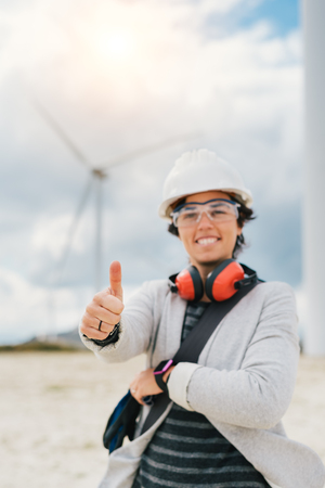smiling engineer woman doing thumbs up sign with safety helmet, gloves, glasses and ear muffs at wind turbine farm generating energy with air flow spinning blades. At work safety first concept.