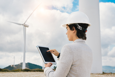 Confident engineer woman touching tablet screen with safety helmet at wind turbine farm in eolic park generating energy with air flow with spinning blades. Clean renewable green wind power concept.