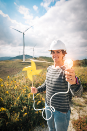 Smiling engineer woman holding handmade paper windmill connected to shining light bulb at a wind power farm plant wearing safety helmet. Sustainable clean green renewable energy concept.