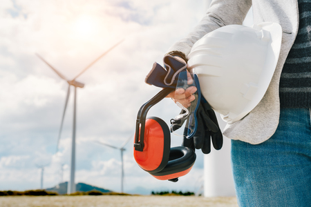 Engineer woman holding safety helmet, gloves, glasses and ear muffs at wind turbine farm generating energy with air flow spinning blades. At work safety first concept. Green clean energy.