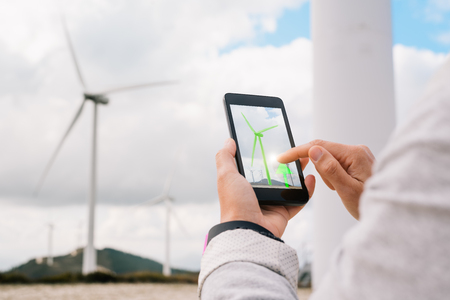 Engineer woman managing energy production app touching phone screen at wind turbine farm park generation with air flow spinning blades. Clean renewable green wind power concept. Banco de Imagens - 66808077