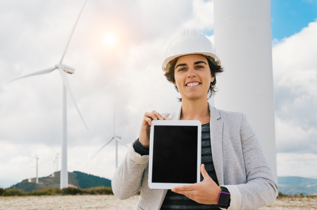 smiling engineer woman showing tablet screen with safety helmet at wind turbine farm in eolic park generating energy with air flow with spinning blades. Clean renewable green wind power concept.
