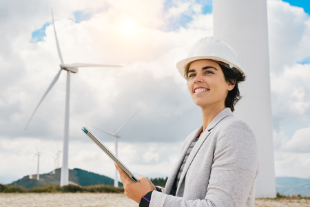 Smiling engineer woman holding tablet with safety helmet at wind turbine farm in eolic park generating energy with air flow with spinning blades. Clean renewable green wind power concept. Banco de Imagens - 67171397