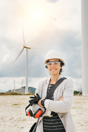 smiling engineer woman crossing arms with safety helmet, gloves, glasses and ear muffs at wind turbine farm generating energy with air flow spinning blades. Clean renewable green wind power concept. Banco de Imagens