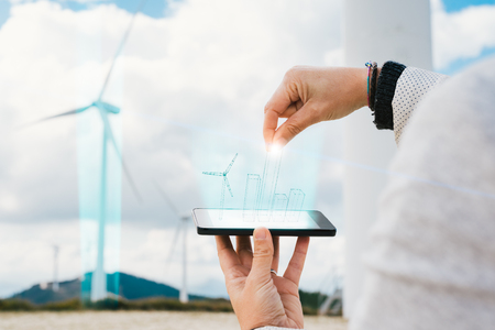 Engineer woman increasing energy production with futuristic hologram on phone screen at wind turbine farm park generation with air flow spinning blades. Clean renewable green wind power concept.