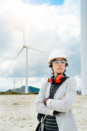 Professional portrait of female engineer after technical maintenance on a wind power generation plant. Woman standing outdoor with safety helmet, gloves, glasses and muffs. Asturias, Spain, Europe.