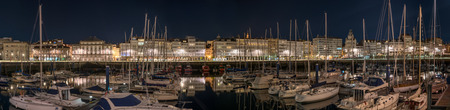 Panoramic night view of touristic sea sport harbor with modernist architecture buildings at down in A Coruña, Galicoa, Spain. Leisure touristic popular postcard must see destination place in Corunna.