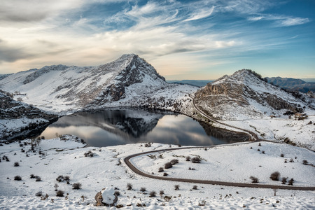 Covadonga lakes beautiful snowy winter landscape scene on a touristic location of Asturias, Spain, Europe, surrounded by mountains. Snow adventure leisure destination for holidays or vacations.