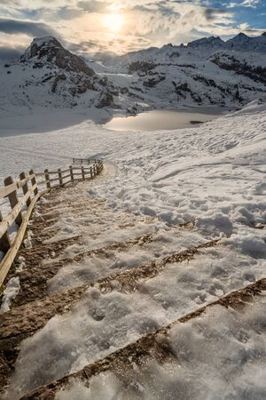 Covadonga lakes beautiful snowy winter landscape scene at Asturias rural location, Spain, Europe, surrounded by mountains. Rock stairs path in snow relax leisure destination for holidays or vacations.