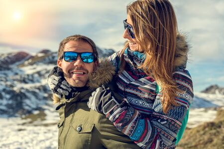 Young hikers couple enjoying vacations in Asturias Somiedo natural park at a snowy mountain beautiful landscape on a sunny day. Successful Healthy man and woman hugging cheerfully looking on holidays.