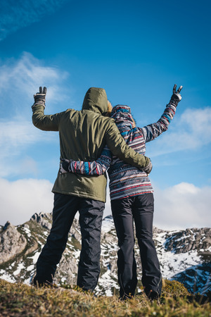 Young couple enjoying vacations in Asturias Somiedo natural park at a snowy mountain beautiful landscape on a sunny day. Man and woman hugging and rising arms doing victory success sign. Banco de Imagens