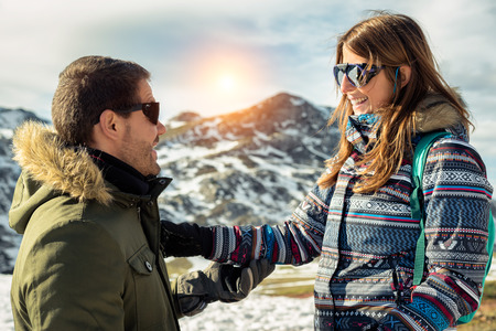 Young couple enjoying vacations in Asturias Somiedo natural park at a snowy mountain beautiful landscape on a sunny day. Man and woman smiling cheerfully looking each other with cool sun glasses. Banco de Imagens