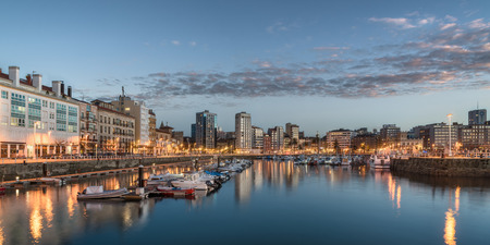 Yatchs and pier in leisure port on maritime fishing district of Gijon, Spain, Europe. Beautiful reflection on calm sea water of boats, buildings, sky at dusk at touristic cultural travel destination.