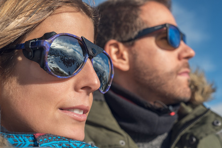 Closeup side view portrait of a pensive couple or marriage together looking to natural snowy landscape with mountain peak reflected on cool sun glasses enjoying sun light, blue sky in the background.
