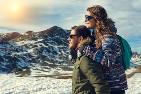 Side view portrait of a pensive couple or marriage hugging and looking to natural snowy landscape wearing gloves, coat and glasses with mountain peak in the background enjoying sun light warmth Banco de Imagens