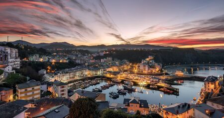 Touristic destination Luarca, Asturias, Spain, Europe. Nature urban landscape with fishing and pleasure port with boats, harbor, sea and beach. Gorgeous red sky at sunset with beautiful sky clouds.