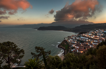 Beautiful view of coastal Asturias sea village Lastres in Spain, Europe during sunset or dusk. Gorgeous panorama of nature traditional famous touristic summer beach destination at dawn.