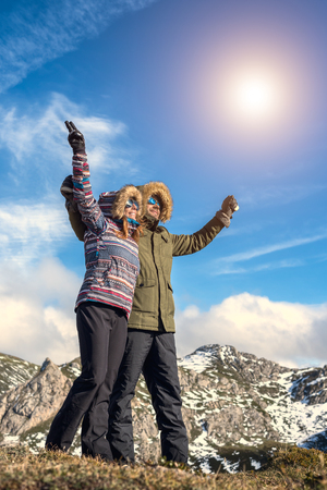 Happy young couple enjoying rural vacations at natural park with snowy mountain beautiful landscape on a sunny day. Cheerful man and woman hugging and rising arms doing victory success sign.