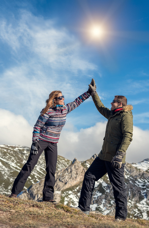 Happy healthy young couple enjoying rural vacations at snowy natural mountain park beautiful landscape on a sunny day. Cheerful man and woman giving five with palms and snow gloves. joyful lifestyle.