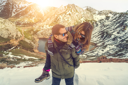 Healthy couple in love vacation concept. Attractive young man and woman playing at snowy nature scene on holidays. Man standing carrying girl on his back looking each other smiling cheerfully. Banco de Imagens