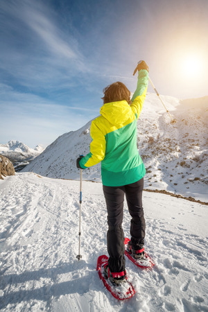 Snowshoeing hiker woman walking outdoor at mountain snowy track on sunny day rising arm in victory success sign in Asturias, Spain. Healthy fit female enjoying tourism nature snow activity lifestyle. Banco de Imagens - 71051905