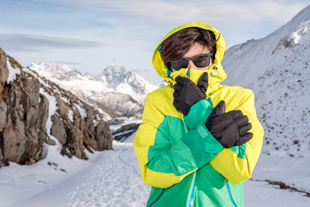 Woman feeling cold discomfort covering her mouth and face from the wind wearing gloves, hood, glasses and windstopper, at extreme snow elements environment on a snowy mountain with low temperature. Banco de Imagens