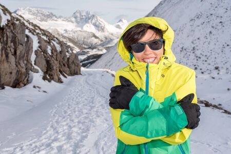 Smiling woman having fun feeling cold hugging herself protecting from the wind wearing gloves, hood, glasses and windstopper while resting on a snowy mountain enjoying hiking outdoor.