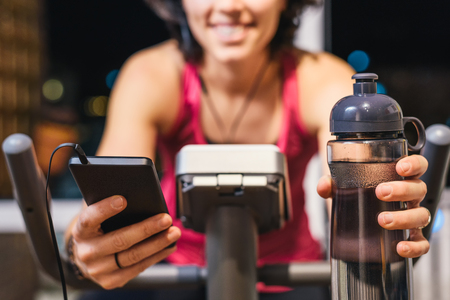 Healthy fit smiling woman training at home on exercise static bike during workout holding phone and bottle of water while listening music with earphones for motivation. Female health weekly habits app Banco de Imagens