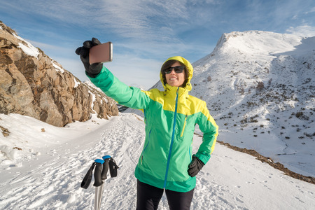 health habits smiling woman taking selfie with phone camera sharing with friends or family. Self picture of Fit female enjoying leisure at mountain snow season vacations. Cell getting in touch people.