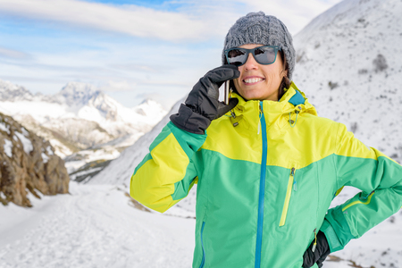 Active healthy smiling woman talking on phone with friends or family. Fit female enjoying snow season vacations on the top of a snowy mountain with gloves and snow hat. smartphone connecting people.
