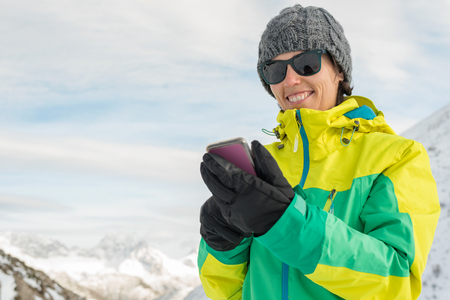 Active healthy smiling woman touching phone screen. Fit female enjoying snow season leisure on the top of a snowy mountain sharing with friends and family. smartphone mobile connecting people.