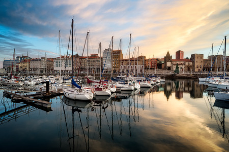Sunrise landscape scenery of Gijon, Spain, Europe. Beautiful reflection on calm sea water of boats, buildings, sky at dusk at touristic cultural travel destination. Banco de Imagens