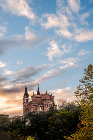 Basilica of Santa Maria la Real de Covadonga, Asturias, Spain, Europe. Beautiful scenery of touristic travel destination in an autumn sunset with a vibrant colorful sky and green forest in mountains.