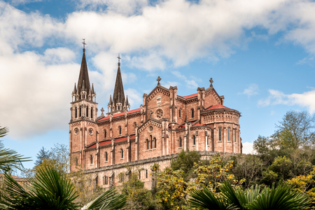 Basilica of Santa Maria la Real de Covadonga, Asturias, Spain, Europe. Beautiful church touristic travel destination landmark with a vibrant colorful sky and green natural foliage.