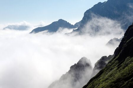 inversion: Steep mountain slopes and low clouds, temperature inversion effect, high mountain peak, above the clouds